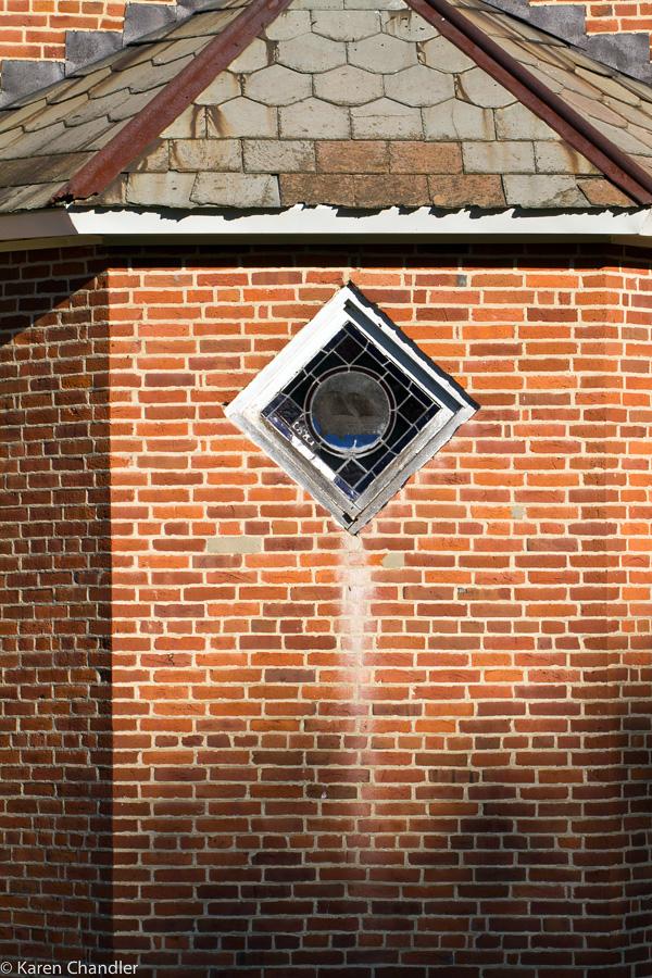 diamond window in old brick church